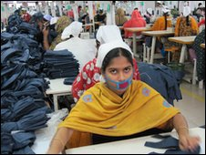 Other workers and piles of jeans in the garment factory