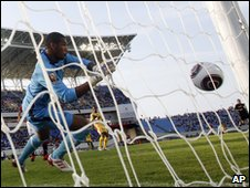 Benin goalkeeper Yoann Djidonou tries to save a shot from Emad Moteab