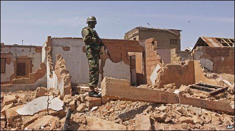 A Nigerian soldier stands in a building that was destroyed in resent violence at Jos