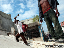 Men try to break through the remains of a collapsed building (19 January 2010)