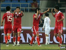 Members of China's national team celebrate after scoring against Vietnam during the Asian Cup football qualifier on 17 January 2010