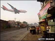 An Air India passenger jet flies over the Jari Mari slum before landing at Mumbai Airport