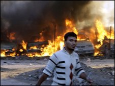 Man walking past December explosion in Baghdad
