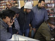 Friends and neighbors gather around a computer seeking news from Haiti in Savoir Faire, a Haitian record store, in New York
