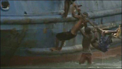 Men climbing up anchor ropes to board the ship