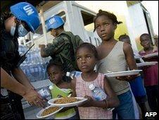 UN peacekeepers distribute food in Cite Soleil, 16 January 2010