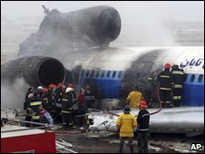 Iranian firefighters work on plane which crash landed at Mashhad airport 24 Jan 2010.