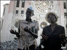 Women pray during an open-air service in Port-au-Prince, 24 Jan