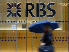 woman walking past the headquarters of the Royal Bank of Scotland in the City of London