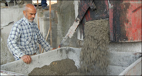 Abdelsalaam Al-Shobaki mixes cement, north Gaza