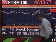 A person walks past a video screen in Kensington, London, displaying the FTSE share index
