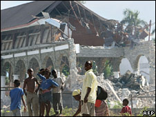 People stay in front of a destroyed church in Leogane, Haiti. Photo: 16 January 2010