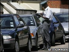 Traffic warden checks parked cars in London