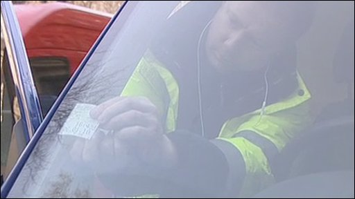 Driver putting a ticket in his car in the City of London