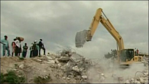 A digger removes rubble from around the collapsed university building