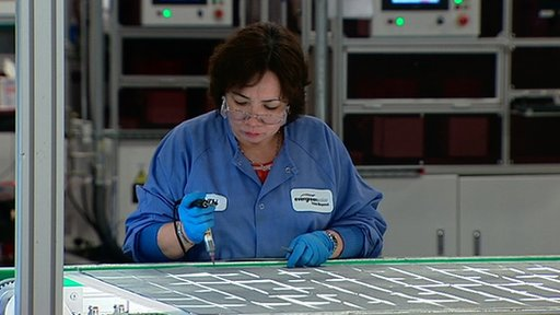 A woman works in a solar panel factory