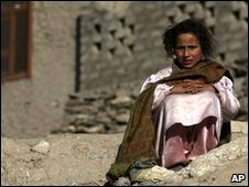 An Afghan girl sits on the ground in front of a house in the Pech Valley, Kunar province, northeastern Afghanistan