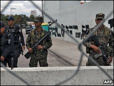 Honduran soldiers patrol the outside of the Brazilian embassy where Manuel Zelaya has  been holed up since September