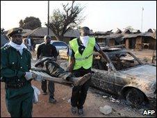 Officials carry a body in Kuru Karam, 21/01