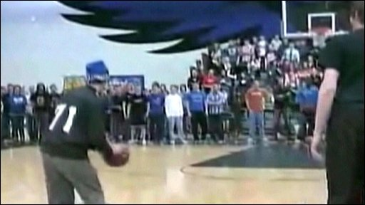 Blindfolded basketball coach Joel Branstrom prepares to shoot