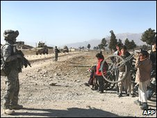 Afghan children stare at a US soldier