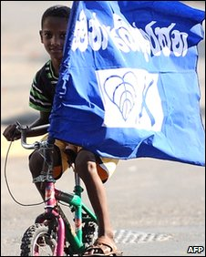 A child cycles with the flag of Sri Lanka's People's Alliance