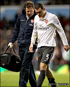 Arsenal defender Thomas Vermaelen leaves the pitch with physio Colin Lewin