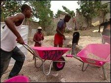 Men in Haiti using pink wheelbarrows