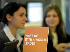 "Staff members nearing a sign which reads: ""Wake up with a world leader"""