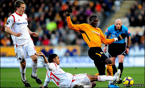 Michael Mancienne gets in an important tackle on Hull's Jozy Altidore