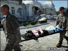 US soldiers evacuate a patient near the ruins of the presidential palace in Port-au-Prince, Haiti, on 23 January 2010