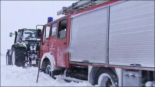 A fire-engine is pulled from the snow in Germany