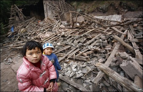 Children stand by the rubble of a house in Moxi, Suining, 31 January