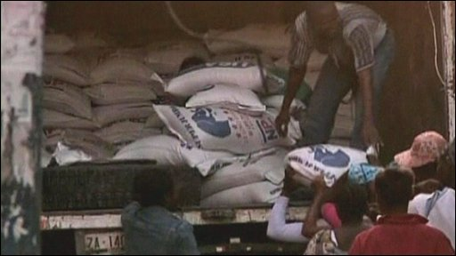 Bags of rice being handed out to women