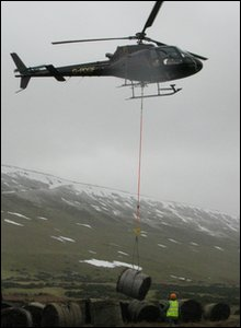 A helicopter airlifting the heather bales