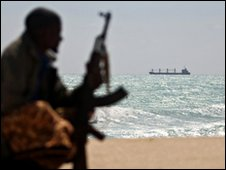 An armed Somali pirate on the coast of Somalia near the town of Hobyo, with the MV Filitsa anchored in the background - photo taken 7 January 2010