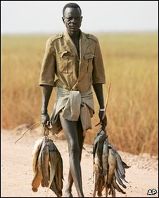 Man carrying fish in south Sudan (file photo)