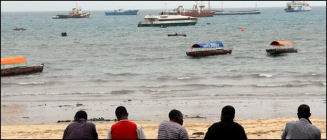 men sitting along the beach in Stone Town, Zanzibar, Tanzania