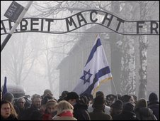 "Visitors pass under a replica ""Arbeit macht frei"" sign at the gate into Auschwitz on the 65th anniversary of the camp's liberation by soldiers of the Soviet Union - 27 January 2010"
