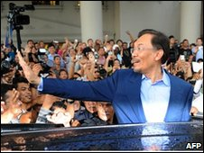 opposition leader Anwar Ibrahim waves to his supporters as he leaves the court house in Kuala Lumpur on February 3
