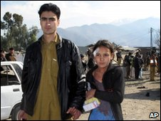 A man escorts an injured girl from the site of the bomb in Lower Dir on 3 February 2010