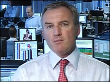 In backgournd, banker looking at image during Channel 7 interview