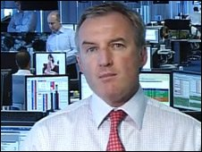 In background, banker looking at image during Channel 7 interview