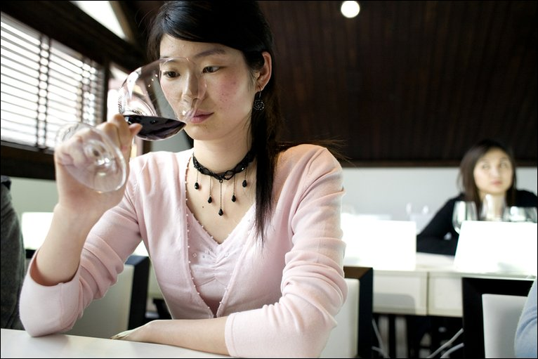 A student inspects wine during a wine education class at the Wine Residence in Shanghai. Photo: Ryan Pyle