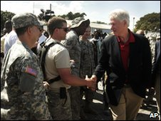 UN special envoy for Haiti and former President Bill Clinton (far right) shakes hands with US soldiers as he visits Port-au-Prince, Haiti