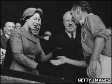 Stanley Matthews receives his medal from the Queen