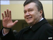Viktor Yanukovych waves to supporters after casting his ballot