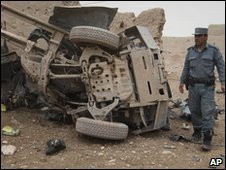 An Afghan policeman walks by wreckage of a police vehicle hit by a bomb in Kandahar on 7 February 2010