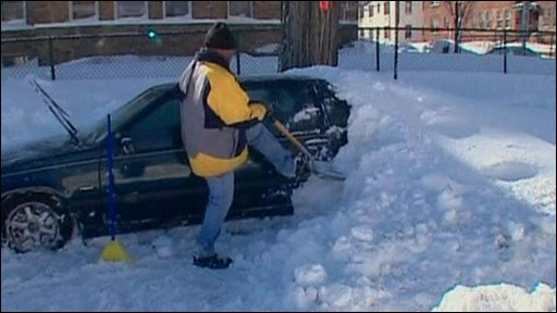 Man digging his car out of the snow