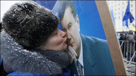 A supporter of Viktor Yanukovych kisses his portrait